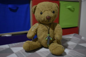 A teddy bear wearing a cross made from beads