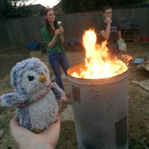 Arnold and 2 humans next to a bonfire